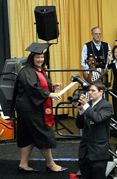 On stage with diploma in hand.