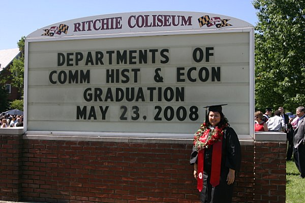 Posing by the sign to mark graduation day.