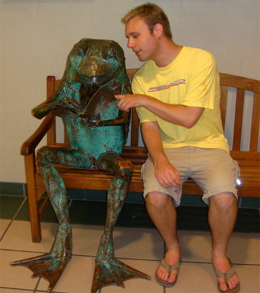 Russell gesturing to a statue of a frog reading on a bench.