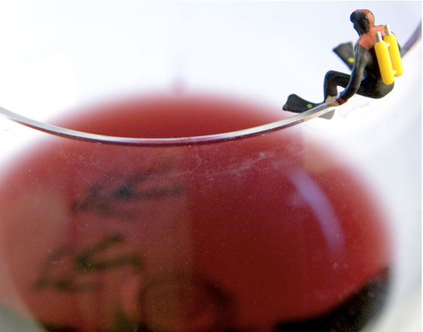 A scuba diver sits on the edge of a wine glass.